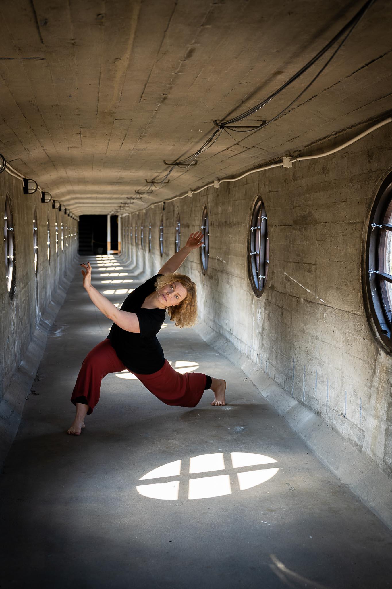 henkilö tanssii betonisessa putkessa punaisissa housuissa